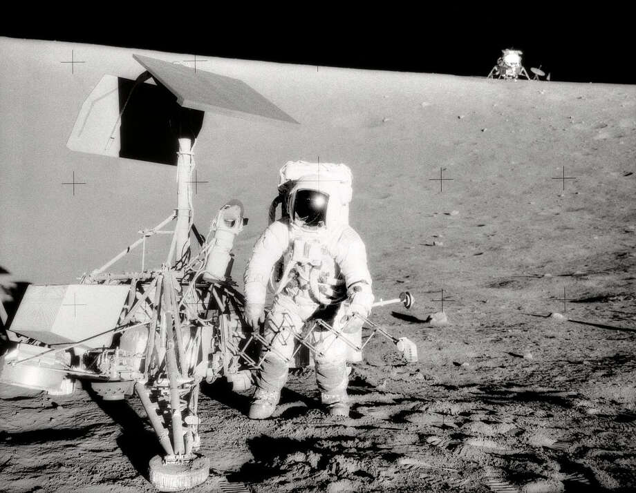 The Apollo 12 lunar module (in the background here) landed about 200 yards away from Surveyor 3, allowing Astronauts Pete Conrad (shown here) and Alan Bean to visit the earlier lander on Nov. 20, 1969. They removed about 22 pounds of parts, including the TV camera, for later examination back on Earth. The Surveyor 3 camera is now on display in the Smithsonian National Air and Space Museum in Washington, D.C. Photo: NASA