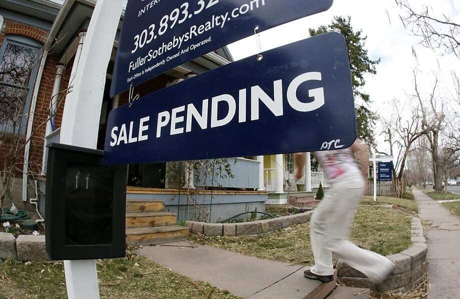 In this Saturday, March 17, 2012, photo, an unidentified woman passes by a pending sale sign outside home on the market in south Denver. A gauge of Americans who signed contracts to buy homes fell in April from nearly a two-year high in the previous month. The decline was the biggest in a year, but sales are still well ahead of last year's level for the same month, suggesting the housing market is improving slowly. (AP Photo/David Zalubowski) Photo: David Zalubowski, Associated Press