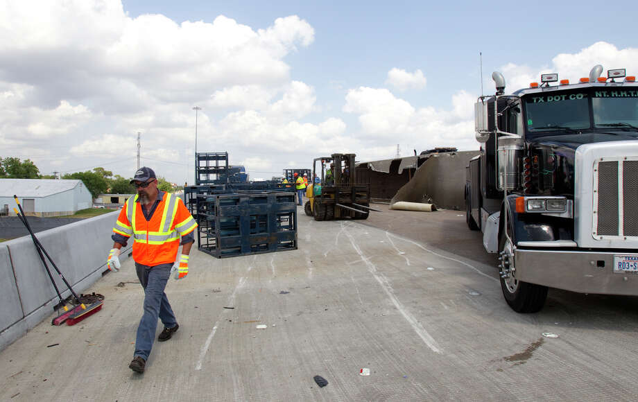 Crews work the scene of an overturned 18-wheeler in the westbound lanes of I-10 Wednesday, May 30, 2012, in Houston. The wreck blocked all but one lane, snarling traffic. Photo: Cody Duty, Houston Chronicle / © 2011 Houston Chronicle