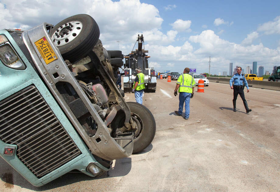 Crews work the scene of an overturned 18-wheeler in the West Bound lane of I-10 Wednesday, May 30, 2012, in Houston. Photo: Cody Duty, Houston Chronicle / © 2011 Houston Chronicle