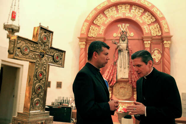 Archbishop Gustavo García-Siller (right) talks with Father Edvin Rodriguez about how people will proceed when they visit San Fernando Cathedral to venerate the relics of the six priests. Photo: Lisa Krantz, San Antonio Express-News / SAN ANTONIO EXPRESS-NEWS