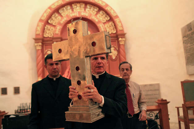 Archbishop Gustavo García-Siller (center) carries the relics of six Knights of Columbus priests to its storage case after a news conference at San Fernando Cathedral on Wednesday, May 30, 2012. Watching are Father Edvin Rodriguez (left) and San Fernando Cathedral Administrator Louis Sanchez. Photo: Lisa Krantz, San Antonio Express-News / SAN ANTONIO EXPRESS-NEWS