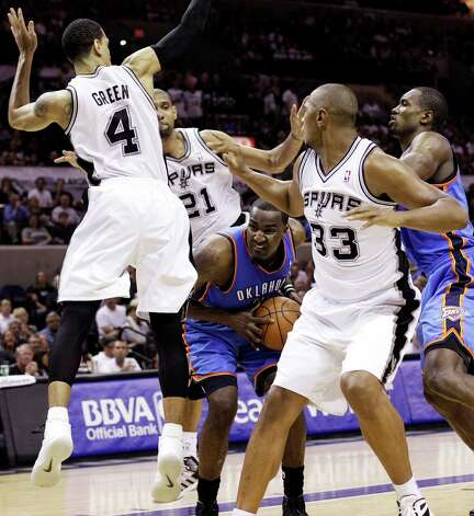 Oklahoma City Thunder center Kendrick Perkins (5) is surrounded by San Antonio Spurs' Danny Green (4), Tim Duncan (21) and Boris Diaw (33) as Thunder's Serge Ibaka (9) watches during the second half of Game 2 in their NBA basketball Western Conference finals playoff series, Tuesday, May 29, 2012, in San Antonio. (AP Photo/Eric Gay) Photo: Eric Gay, STF / AP