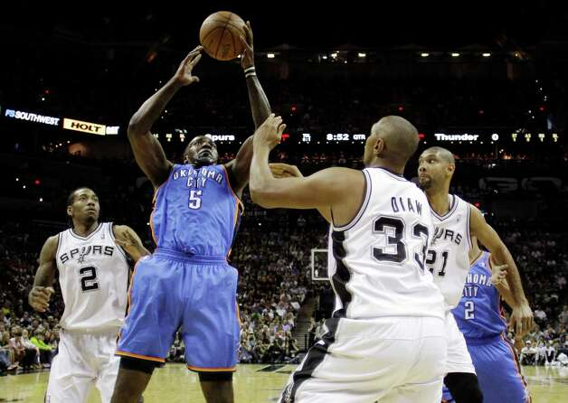 Oklahoma City Thunder center Kendrick Perkins (5) is guarded by San Antonio Spurs' Kawhi Leonard (2), Boris Diaw (33) and Tim Duncan (21) during the first half of Game 2 in their NBA basketball Western Conference finals playoff series, Tuesday, May 29, 2012, in San Antonio.(AP Photo/Eric Gay) Photo: Eric Gay, STF / AP