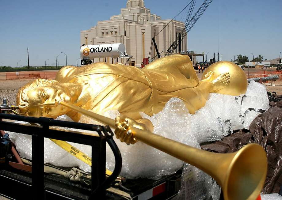 A Moroni angel statue is lifted with cranes, Tuesday, May 15, 2012, to be placed on the spire of the Gilbert Temple the southeast corner of Pecos and Greenfield Roads in Gilbert, Ariz. Moroni is an iconic symbol of The Church of Jesus Christ of Latter-day Saints and is used on most of the Mormon temples worldwide. Hundreds of people turned out to see the angle put into place. (AP Photo/East Valley Tribune, Tim Hacker) ARIZONA REPUBLIC OUT; MANDATORY CREDIT Photo: Tim Hacker, Associated Press