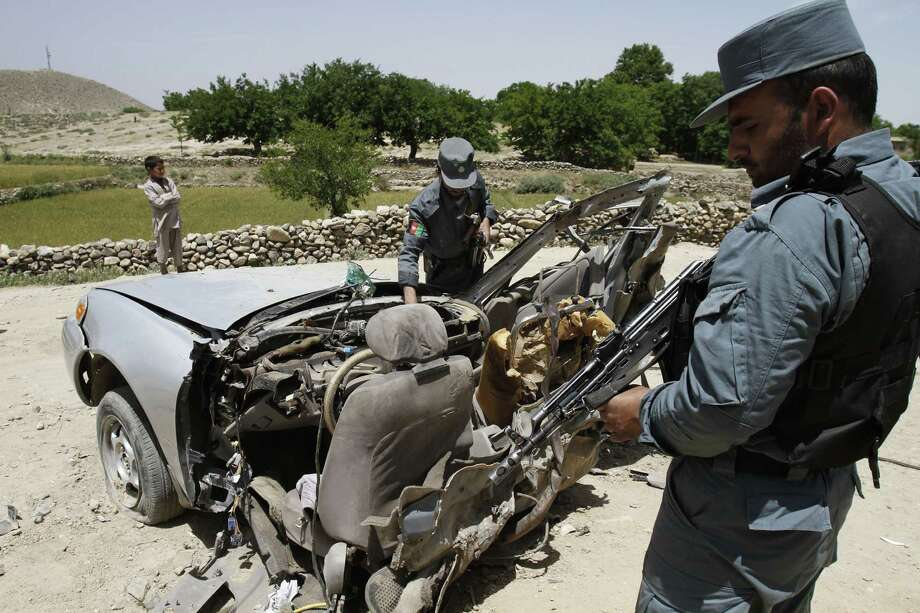 Afghan policemen examine the remains of a damaged vehicle after it was hit by a road side bomb in Deh Bala district of Jalalabad east of Kabul, Afghanistan, Wednesday, May 30, 2012. Three district government employees were killed by a roadside bomb as they were traveling to work Wednesday morning in eastern Nangarhar province's Deh Bala district, said district chief Asrarullah. Photo: Rahmat Gul, Associated Press / AP