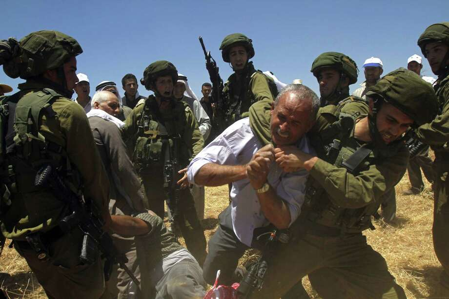 An Israeli soldier scuffles with a Palestinian farmer Wednesday as the military prevents villagers from working their lands in the West Bank village of Tuqua. Photo: MUSA AL-SHAER / AFP