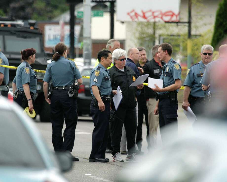 Seattle Police officers confer outside Cafe Racer, where a gunman opened fire, killing four people and wounding one other on May 30, 2012 in Seattle. Photo: AP