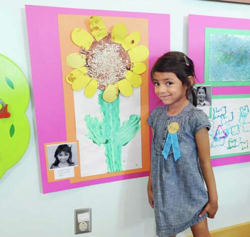 Frida Lemus, 4, of Greenwich, with her artwork of a sunflower during the Family Centers' Head Start Preschool art show in the Children's Room at Greenwich Library, Wednesday, May 30, 2012. Photo: Bob Luckey / Greenwich Time