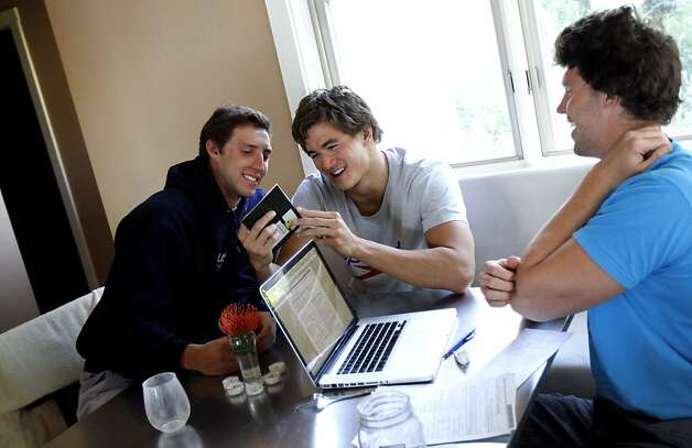 Swimmers Will Copeland, 26, left, and Nathan Adrian, 23, center, check out the passport photo of Graeme Moore, 23, right, at home in Berkeley, Calif. Monday, May 28, 2012.  The three are training for the Olympics along with fellow swimmer Sean Mahoney, 23, and all four have been sharing a house. Photo: Sarah Rice, Special To The Chronicle