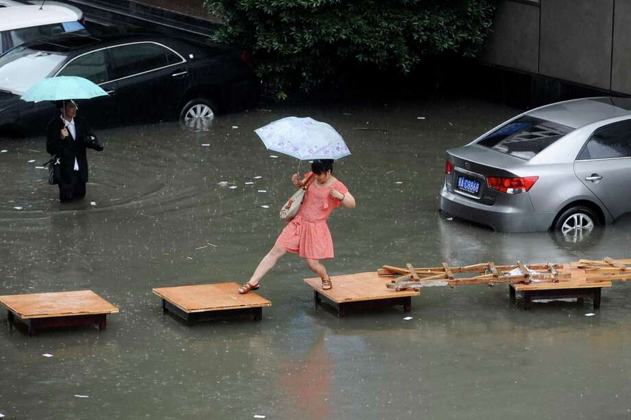 A woman crosses a flooded street on a row of tables in Wuhan, central China's Hubei province. China is hit by big summer rainfalls every year, as heavy downpours across large swathes of the country trigger flooding, landslides and other rain-related disasters. Photo: AFP, AFP/Getty Images / AFP