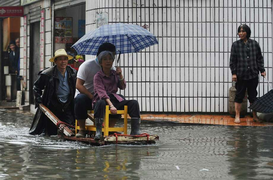 A vendor uses his cart to ferry residents across a flooded street in Wuhan, central China's Hubei province. Photo: AFP, AFP/Getty Images / AFP