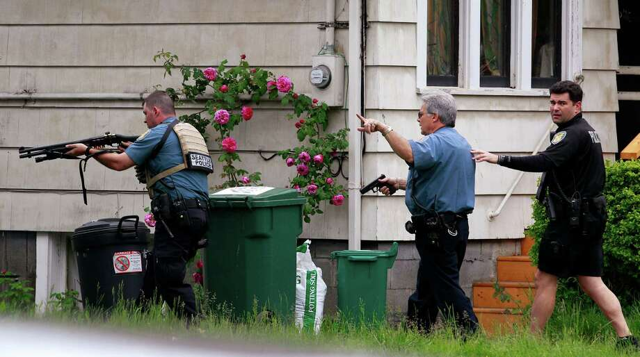 Police surround a house in Seattle near a cafe where a gunman killed three people and wounded two others on Wednesday. A fourth person was killed earlier. Photo: Elaine Thompson / AP
