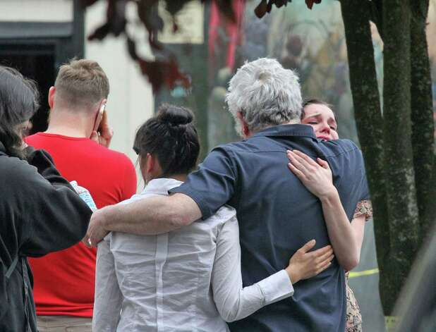 Onlookers console one another outside Cafe Racer Espresso where Seattle police say two are confirmed dead and three others are wounded, one with life-threatening injuries, Wednesday, May 30, 2012, in Seattle, Washington. Photo: Greg Gilbert, McClatchy-Tribune News Service / Seattle Times