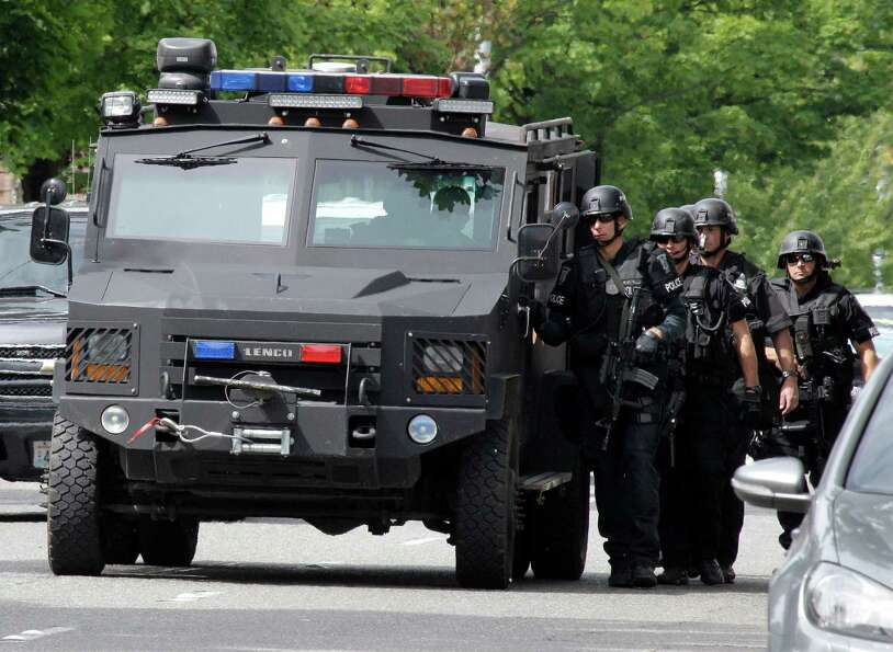 A Seattle Police SWAT team uses a vehicle for protection as they walk to a house in the neighborhood