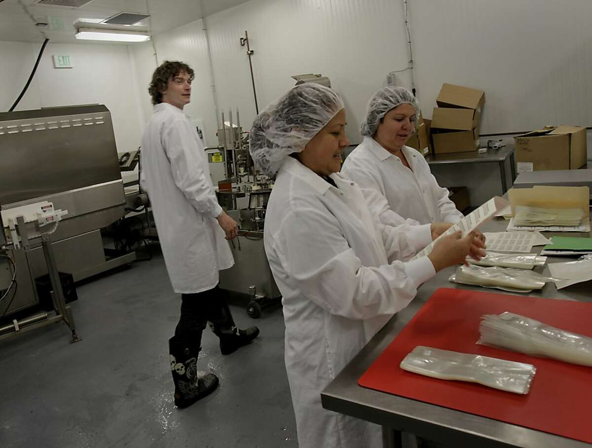 Founder Neal Gottlieb (left) walks by a production line where workers are making labels for ice cream sandwiches. Three Twins Ice Cream is a local company that makes organic ice cream. Founder Neal Gottlieb visited the Petaluma, Calif. plant where they produce the ice cream Wednesday May 30, 2012.
