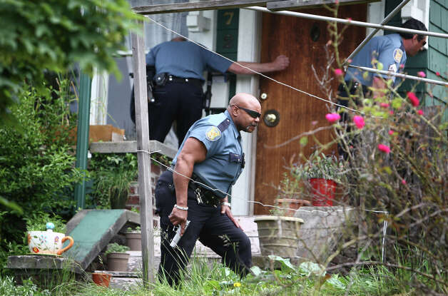 Seattle Police officers search yards and go door to door after five people were shot at Cafe Racer on Roosevelt Way NE in Seattle. Four of the victims died from the violence. Another person was shot and 