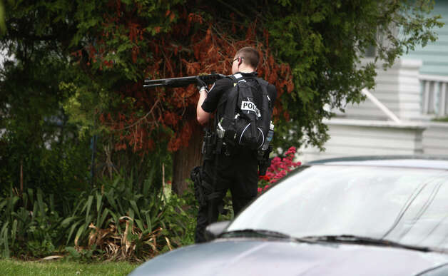 An officer doing a door to door sweep aims his weapon into a yard after five people were shot at Cafe Racer. Photo: JOSHUA TRUJILLO / SEATTLEPI.COM