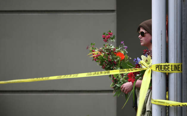 People bring flowers after five people were shot at Cafe Racer on Roosevelt Way NE. Photo: JOSHUA TRUJILLO / SEATTLEPI.COM