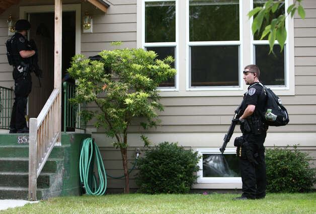 Seattle Police officers search yards and go door to door after five people were shot at Cafe Racer on Roosevelt Way NE. Photo: JOSHUA TRUJILLO / SEATTLEPI.COM