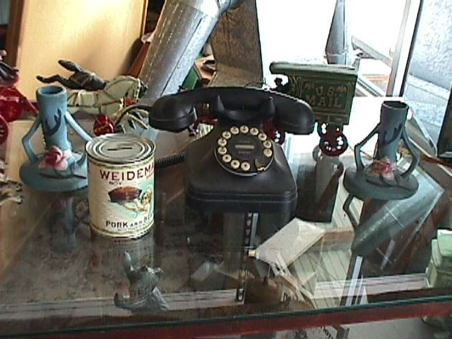 Some of the reproductions Bill Johns will discuss on June 13 include a fake piece of Roseville pottery, a tin can bank with a fake early paper label, a fake cast iron toy, and a modern phone in the old style.