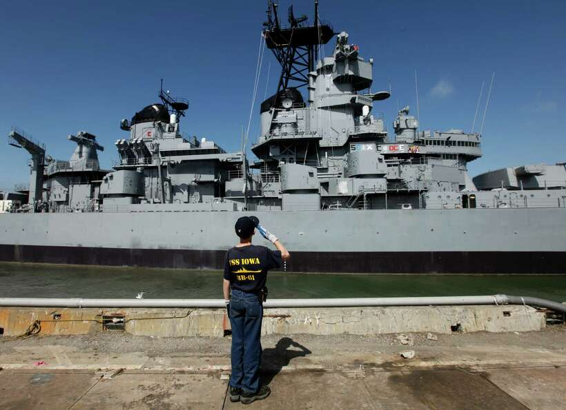 Jonathan Canfield, 12, salutes as the USS Iowa is towed from the Port of Richmond on Saturday, May 2
