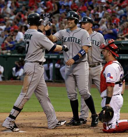 Seattle Mariners' Justin Smoak, left, is congratulated by Jesus Montero and Kyle Seager, center rear, as Texas Rangers catcher Mike Napoli, right, watches following Smoak's three-run home run off of Rangers relief pitcher Yoshinori Tateyama in the third inning of baseball game on Wednesday, May 30, 2012, in Arlington, Texas. Photo: AP