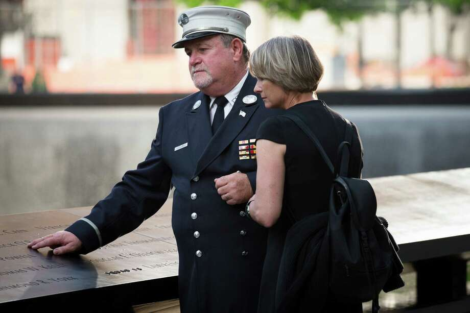 Retired FDNY Lt. Jerry Collins and his wife Suzanne Collins pause at the 9/11 Memorial, Wednesday, May 30, 2012, in New York. Recovery workers and first responders were invited to the memorial to be honored on the 10-year anniversary of the conclusion of clean-up efforts that stretched nine months until May 30, 2002. Photo: John Minchillo, Associated Press / AP