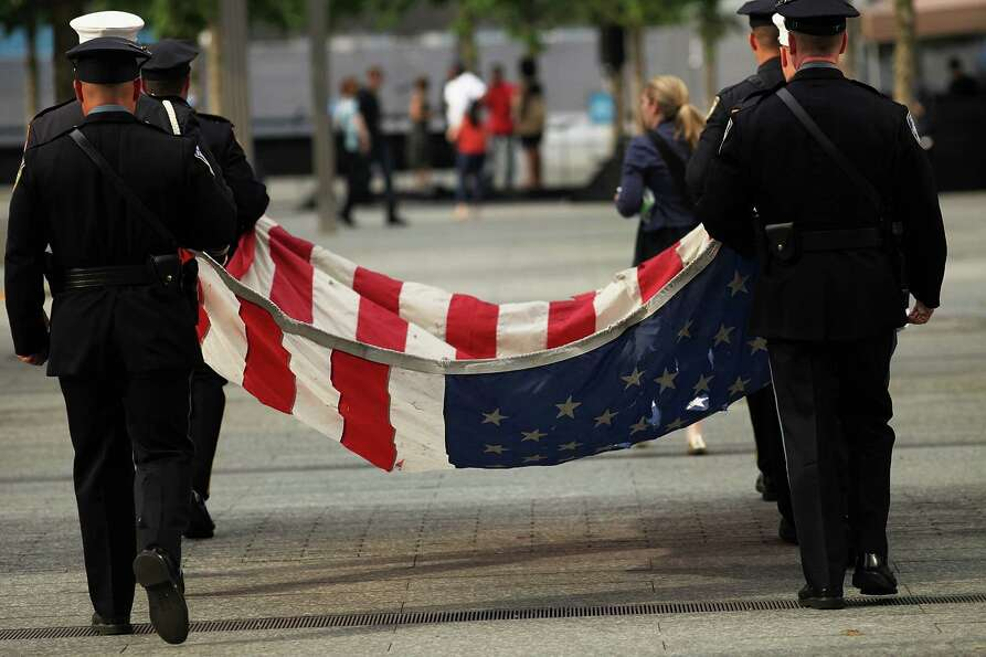 New York City firefighters and police officers participate in a tribute at the 9/11 Memorial for rec