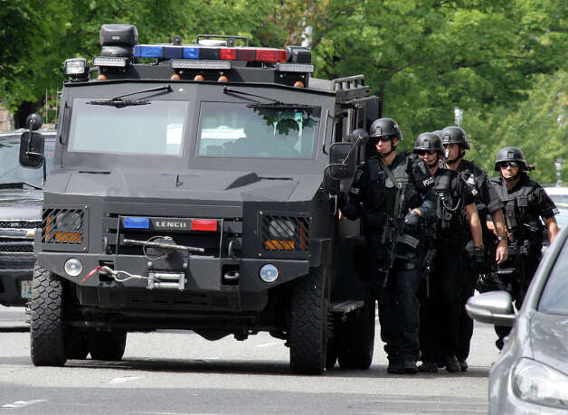 A Seattle Police SWAT team uses a vehicle for protection as they walk to a house where a shooting suspect was said to have previously lived. Photo: Ted S. Warren / Associated Press