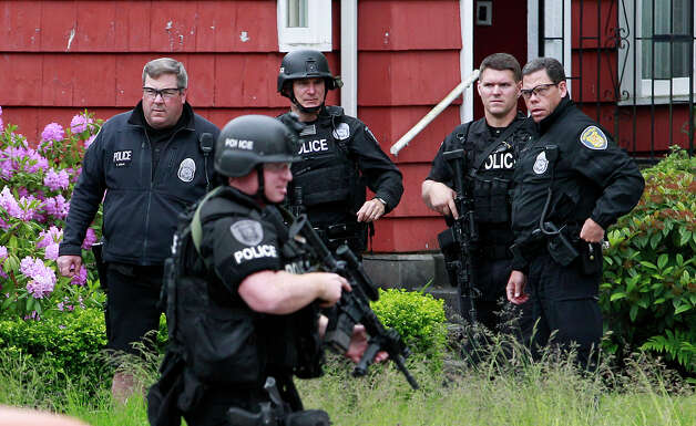 Police stand near a house in the University district in Seattle close to the cafe where a gunman killed three people. Photo: Elaine Thompson / Associated Press
