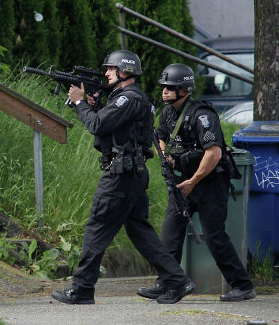 Two members of a Seattle Police SWAT team walk to a house where a suspect was said to have previously lived. Photo: Ted S. Warren / Associated Press
