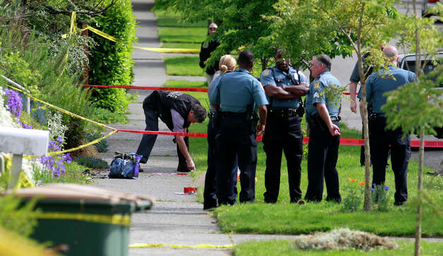 Police investigate the scene where a man who was believed to have shot and killed several people earlier in the day shot himself Wednesday, May 30, 2012, in West Seattle. Photo: Elaine Thompson / Associated Press