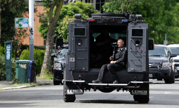 A Seattle Police SWAT team member drives down a street after officers searched a house in the neighborhood where a shooting took place in Seattle. Photo: Ted S. Warren / Associated Press