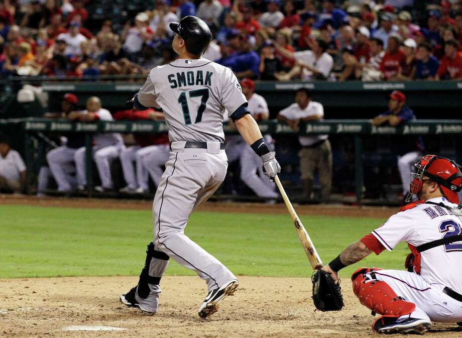 Seattle Mariners' Justin Smoak (17) follows through on a three-run home run off Texas Rangers' Koji Uehara as catcher Mike Napoli watches in the eighth inning of baseball game, Wednesday, May 30, 2012, in Arlington, Texas. The Mariners won 21-8. Photo: AP