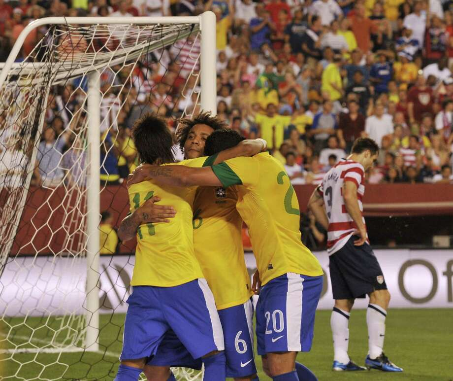 Marcelo (C) of Brazil is congratulated by teammates during an international friendly with the US at FedEx Field in Landover, Maryland, on May 30, 2012.  Brazil won 4-1.  AFP PHOTO/Nicholas KAMMNICHOLAS KAMM/AFP/GettyImages Photo: NICHOLAS KAMM, AFP/Getty Images / AFP