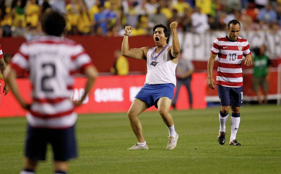 LANDOVER, MD - MAY 30: A fan celebrates on the field in front Michael Parkhurst #2 and Landon Donova