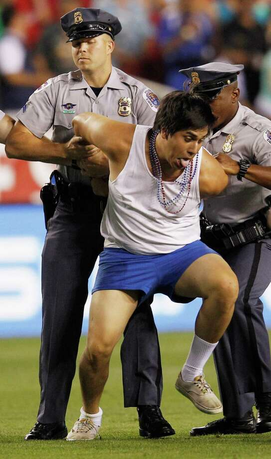 LANDOVER, MD - MAY 30:  Police detain a fan who ran onto the field after Brazil scored a goal during their 4-1 win over USA in an International friendly game at FedExField on May 30, 2012 in Landover, Maryland. Photo: Rob Carr, Getty Images / 2012 Getty Images