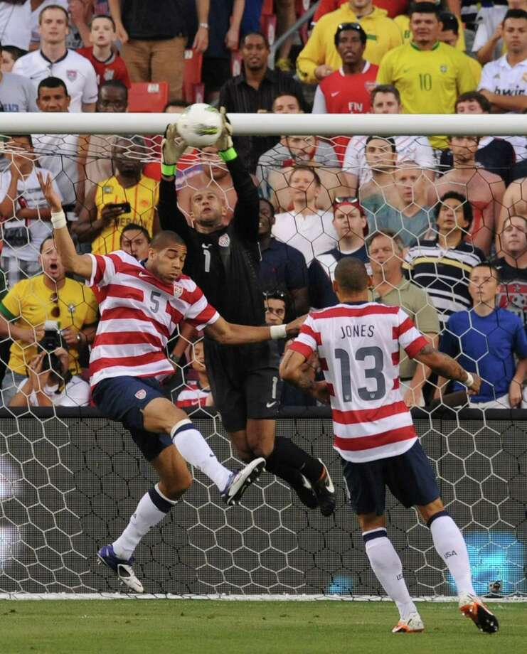 US goalkeeper Tim Howard (C) makes the save before teammates Oguchi Onyewu (L) and Jermaine Jones (R) during an international friendly with Brazil at FedEx Field in Landover, Maryland, on May 30, 2012.   AFP PHOTO/Nicholas KAMMNICHOLAS KAMM/AFP/GettyImages Photo: NICHOLAS KAMM, AFP/Getty Images / AFP