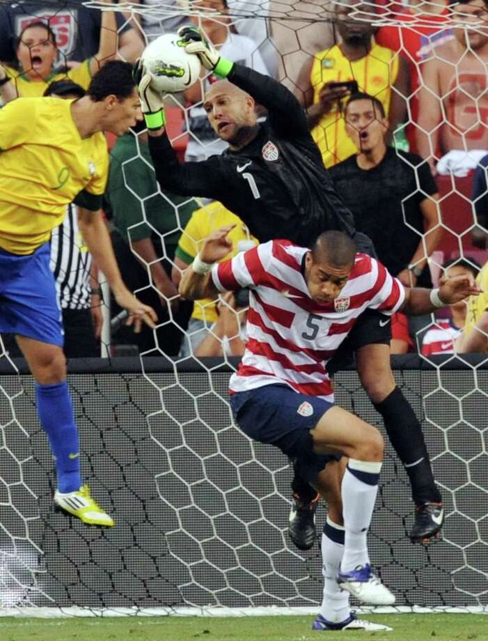 US goalkeeper Tim Howard (C) makes the save before teammate Oguchi Onyewu (R) and Brazil's Leandro Damaio (L) during an international friendly at FedEx Field in Landover, Maryland, on May 30, 2012.   AFP PHOTO/Nicholas KAMMNICHOLAS KAMM/AFP/GettyImages Photo: NICHOLAS KAMM, AFP/Getty Images / AFP
