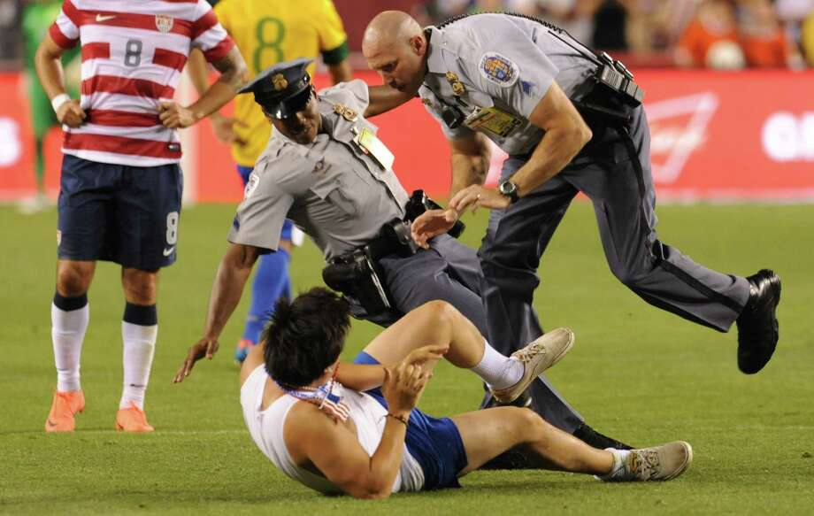 A fan who ran onto the field is arrested during an international friendly between the US and Brazil at FedEx Field in Landover, Maryland, on May 30, 2012.  Brazil won 4-1.  AFP PHOTO/Nicholas KAMMNICHOLAS KAMM/AFP/GettyImages Photo: NICHOLAS KAMM, AFP/Getty Images / AFP