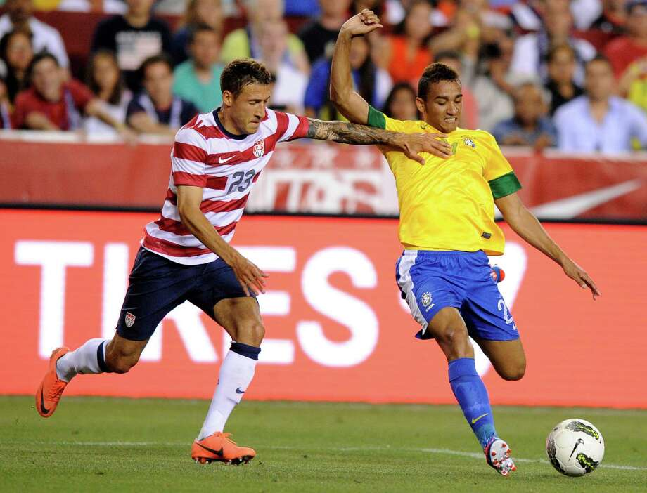 United States' Fabian Johnson (23) tries to stop Brazil's Danilo, right, during the second half of an international friendly soccer game on Wednesday, May 30, 2012, in Landover, Md. Brazil won 4-1. (AP Photo/Nick Wass) Photo: Nick Wass, Associated Press / FR67404 AP