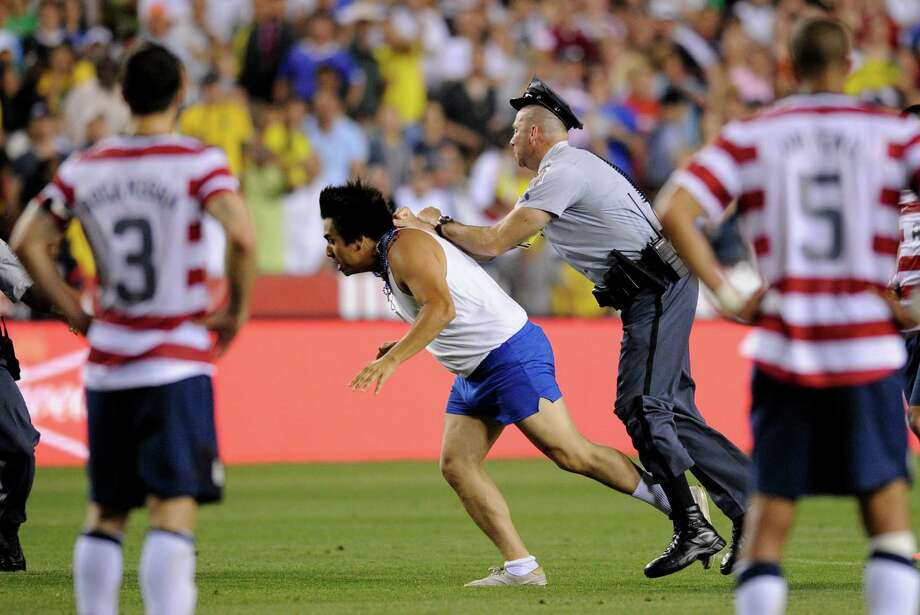A police officer goes after a man who ran onto the field as United States' Carlos Bocanegra (3) and Oguchi Onyewu (5) watch during the second half of an international friendly soccer game against Brazil, Wednesday, May 30, 2012, in Landover, Md. Brazil won 4-1. (AP Photo/Nick Wass) Photo: Nick Wass, Associated Press / FR67404 AP