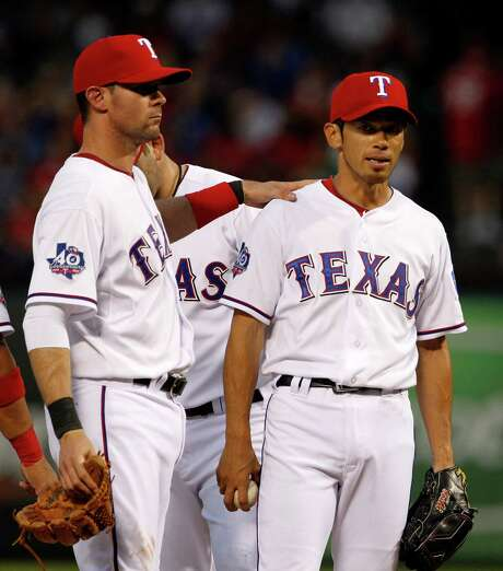 The Rangers' Michael Young, left, consoles reliever Yoshinori Tateyama, who gave up eight runs in the third inning after Texas starter Derek Holland surrendered eight in the third. Photo: Tony Gutierrez / AP
