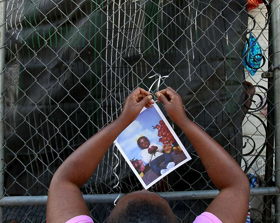 Rachell Allen, great aunt to five year old Brianna Allen, who was killed by gunfire, hangs pictures of Brianna with ribbon, at the scene where four people were shot, in New Orleans, Wednesday, May 30, 2012. The shooting was part of a string of violence that rocked New Orleans on Tuesday, leaving three people dead and six others wounded in four separate incidents. (AP Photo/Gerald Herbert) Photo: Gerald Herbert, Associated Press