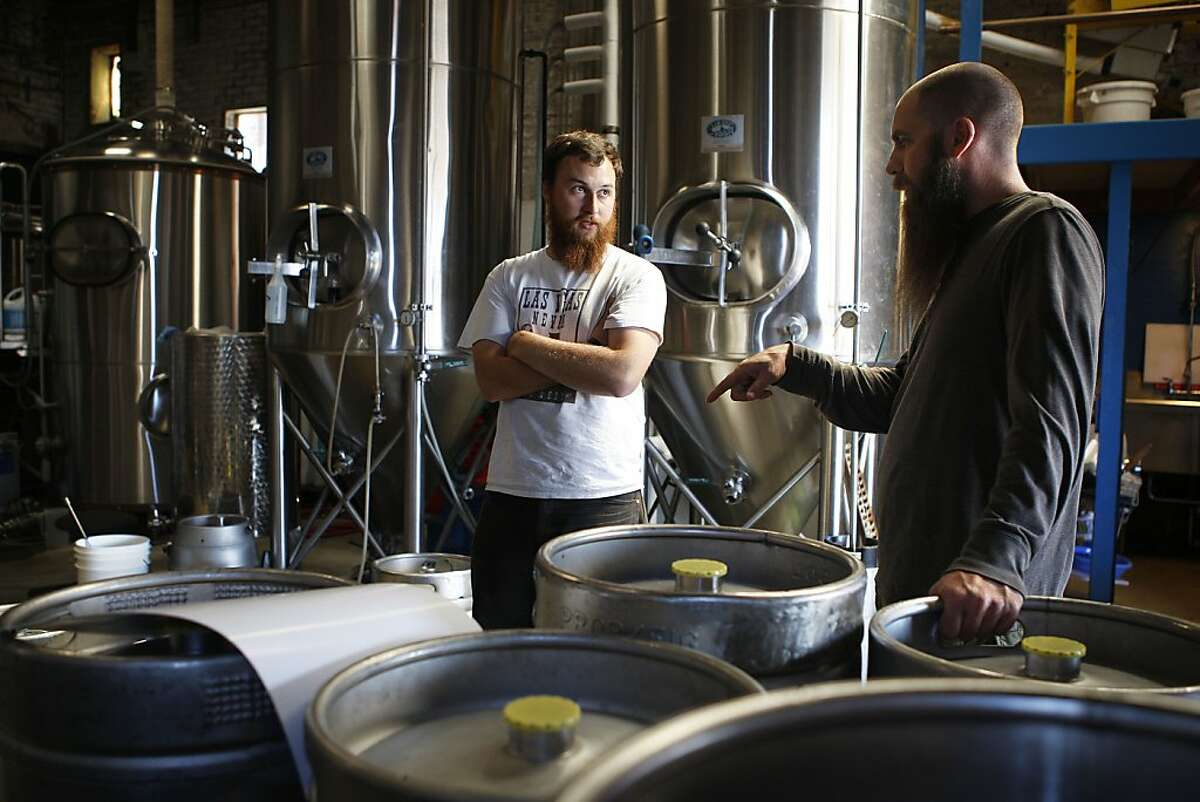 Lead brewer Andrew Ritter (left) and founder Adam Lamoreaux (right) discussing deliveries at the Linden Street Brewery in Oakland, California, on Tuesday, May 22, 2012.