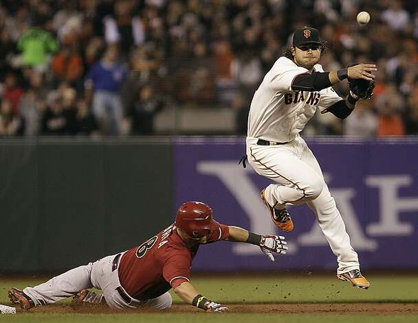 San Francisco Giants shortstop Brandon Crawford, right, throws over Arizona Diamondbacks' Gerardo Parra to complete a double play in the fifth inning of a baseball game on Wednesday, May 30, 2012, in San Francisco. Arizona's Willie Bloomquist was out at first base. (AP Photo/Ben Margot) Photo: Ben Margot, Associated Press