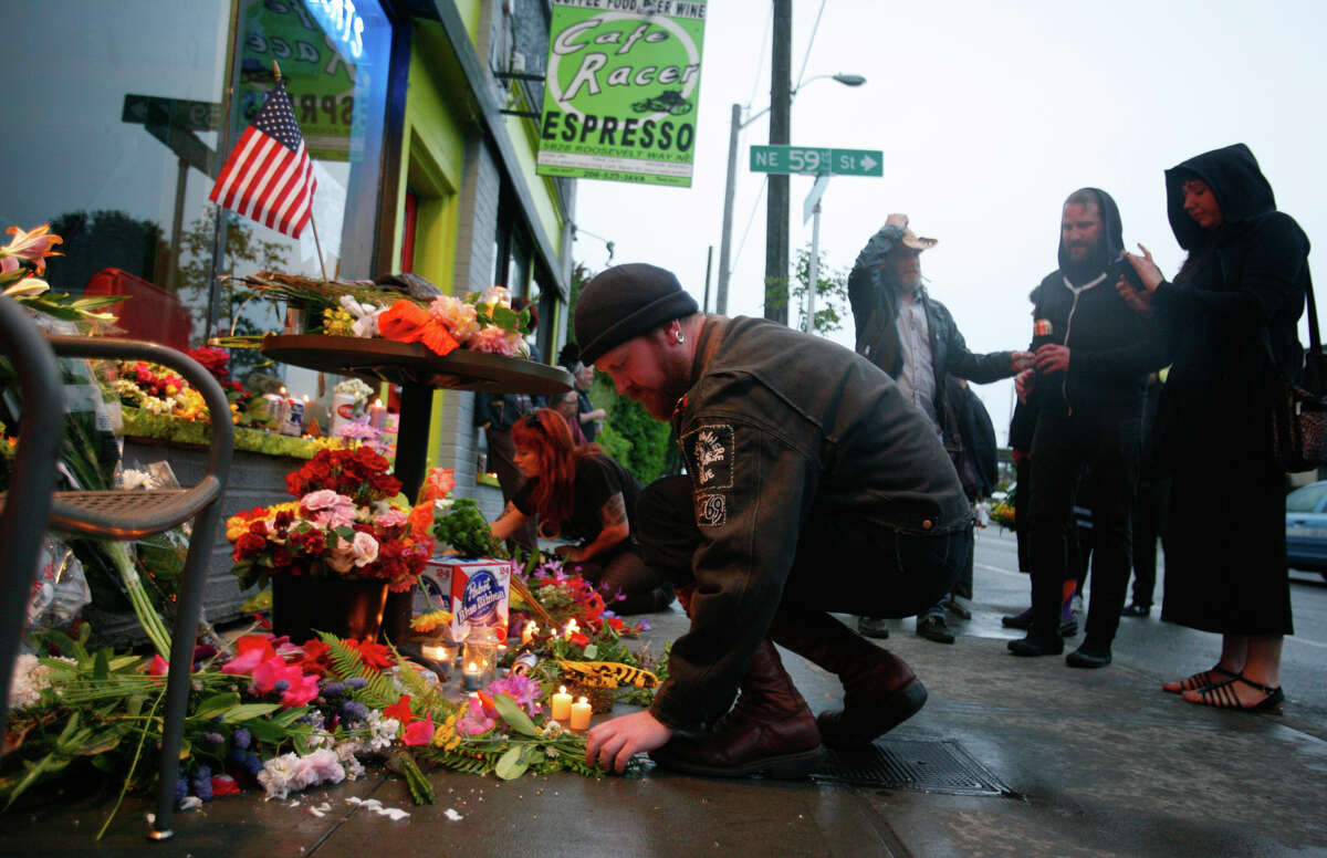 Flowers and candles are placed in front of the Cafe Racer after five people were shot at the Seattle cafe on Wednesday, May 30, 2012. Four of the victims died from the violence. A fifth person was shot and killed in downtown Seattle about 30 minutes later. Seattle Police said they believed it was by the same suspect. The suspect later shot himself in West Seattle.