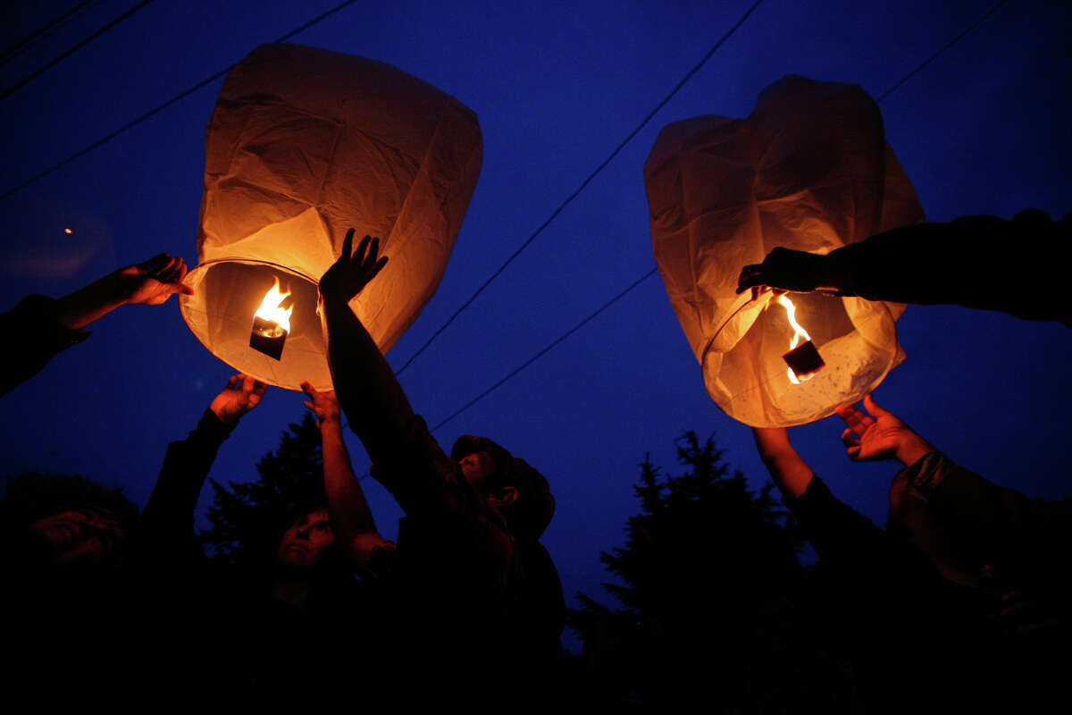 Floating lanterns are lit during a vigil after five people were shot at Cafe Racer on Roosevelt Way NE in Seattle. Four of the victims died from the violence. A fifth person was shot and killed in downtown Seattle about 30 minutes later. Seattle Police said they believed it was by the same suspect. The suspect later shot himself in West Seattle.