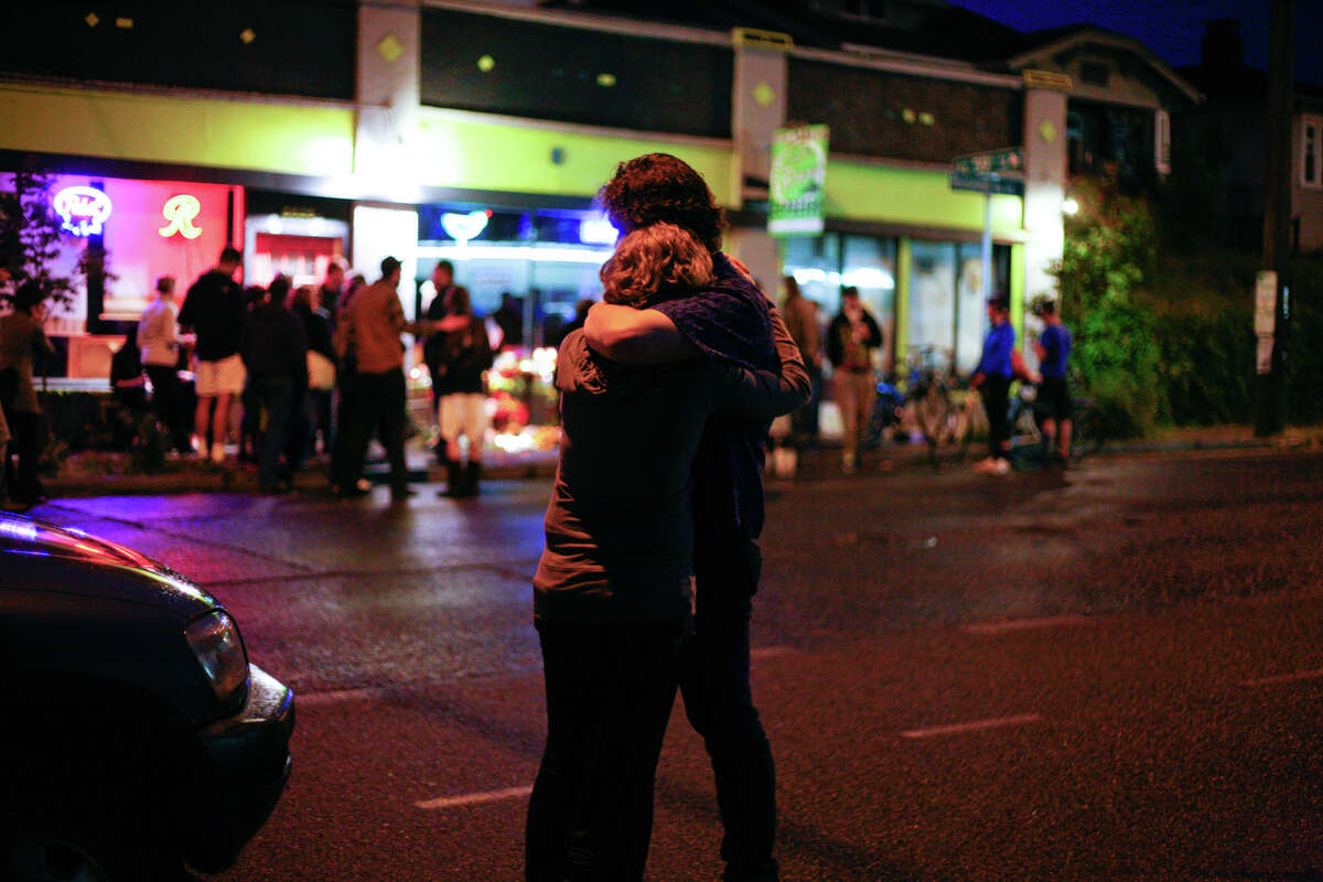 People grieve on May 30, 2012 after five people were shot at Cafe Racer on Roosevelt Way NE in Seattle on Wednesday.